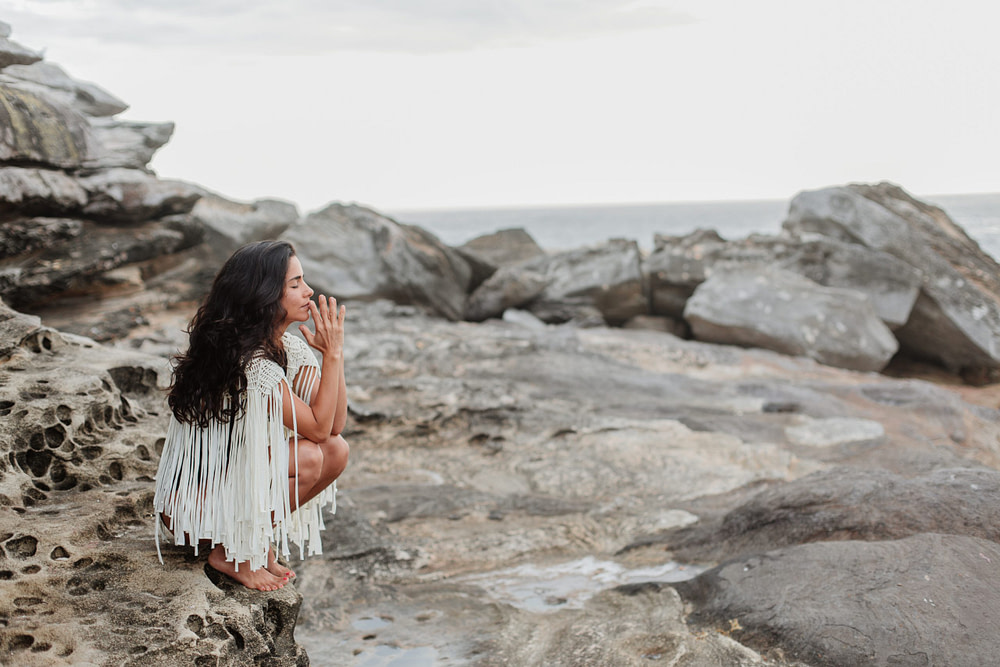 woman sitting on rocky beach